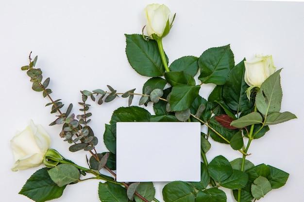 碑文メモとバラの花の紙カードで作られた創造的なモックアップレイアウト。フラット横たわっていた結婚式やバレンタインデーの最小限のコンセプト。