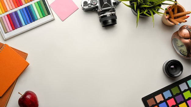Creative mock up scene, designer workspace with paint tools, camera, stationery and copy space, top view