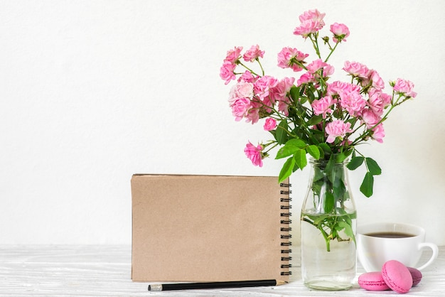 Creative mock up with a beautiful bouquet of pink roses flowers, coffee cup, macaroons and blank hipster notebook