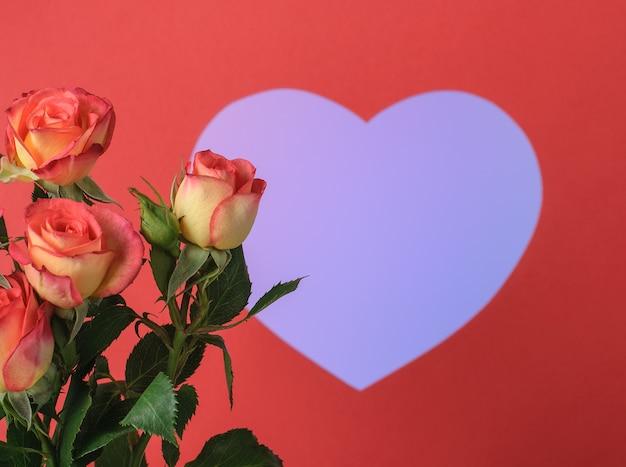 Креативный макет из розовых цветов и бумажной красной рамки в форме сердца