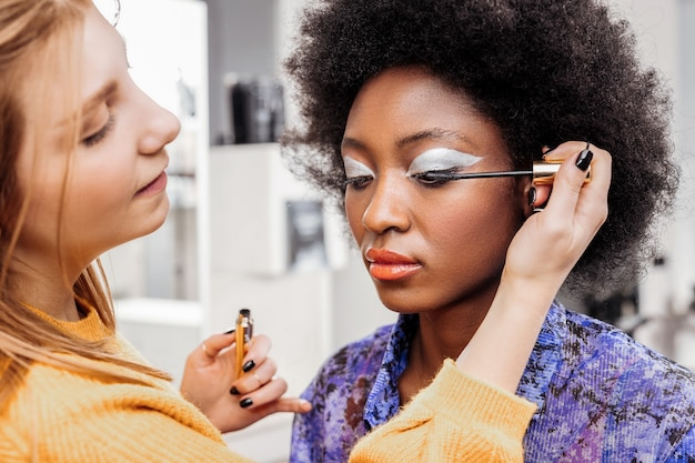 Creative mood. fair-haired young stylist with black nail polish feeling creative doing makeup to a model