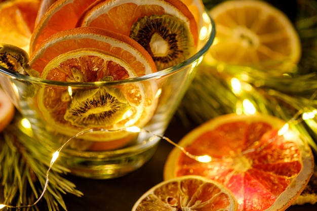 Creative moody holiday christmas new year food fruits with dried grapefruit, kiwi, orange and lemon in glass bowl