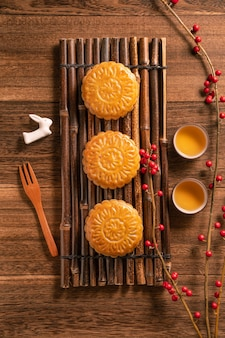 Creative moon cake mooncake table design - chinese traditional pastry with tea cups, mid-autumn festival concept, top view, flat lay.