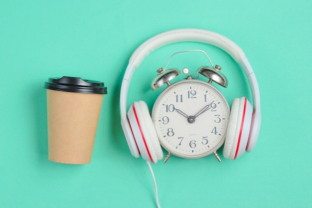 Creative music concept. retro alarm clock with classic headphones and coffee cup on blue background.