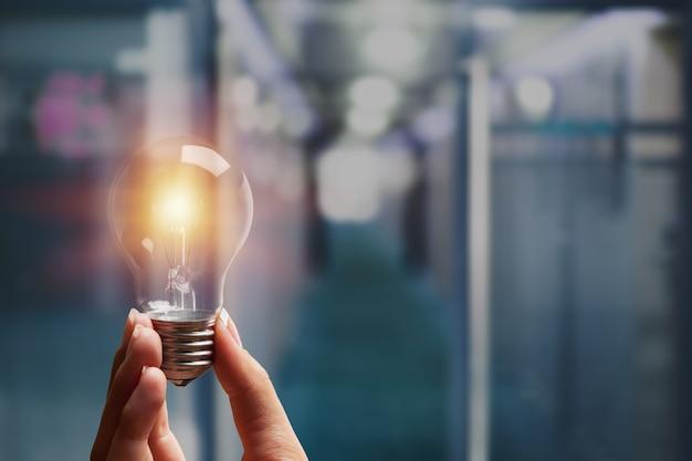 Творческая новая идея. мужчина держит лампочку.