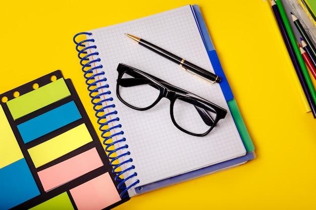 Креативная концепция офиса с красочными поставками на желтом столе