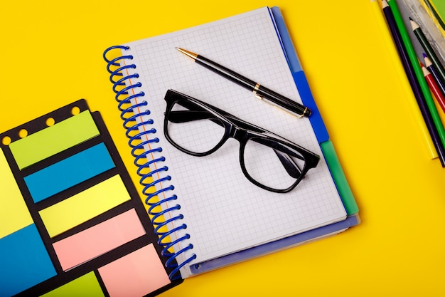Creative office concept with colorful supplies on yellow table