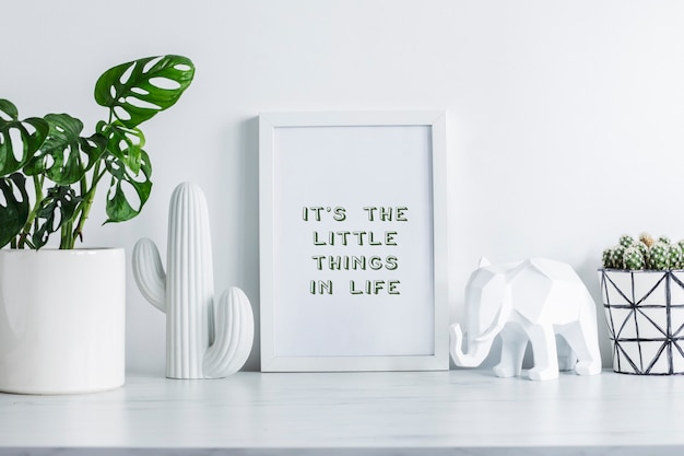 흰색 모의 프레임이 있는 스칸디나비아 스타일의 창의적인 사무실 책상, 힙스터 디자인 냄비에 선인장, 클래식 냄비에 식물, 선인장과 코끼리의 흰색 인물. 흰색 최소한의 개념입니다.