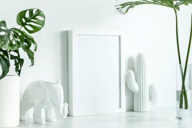 흰색 모의 포스터 프레임, 선인장과 코끼리의 흰색 인물, 유리 꽃병에 나뭇잎이 있는 스칸디나비아 스타일의 창의적인 사무실 책상. 흰색 최소한의 개념입니다.