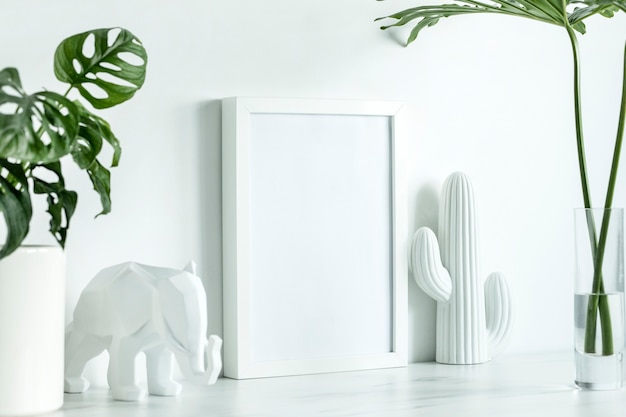 Creative office desk in scandinavian style with white mock up poster frame, white figures of cacti and elephant, leaves in glass vase. white minimalistic concept.