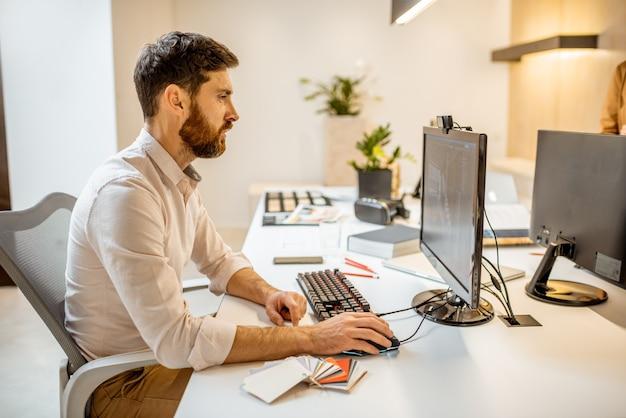 Креативный офисный работник, занимающийся дизайном интерьера, 3d моделирование на компьютере, сидя в современном офисе архитектурной фирмы
