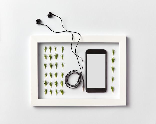 Креативный ogranic травяной узор из веточек хвои, мобильный смартфон с пустым экраном для макета и наушники в рамке на светло-серой стене. место для текста. плоская планировка.