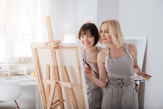 クリエイティブアウトレット。一緒に立って、活動を楽しみながら絵を描く素敵な楽しい若い女性