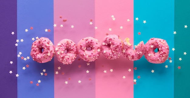 Creative panoramic image of flying tasty pink donuts, one already half eaten. conceptual levitation of sweet delicious dooughnuts on layered multicolored paper background.