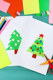 Креативная бумажная новогодняя елка на листе белой бумаги, ножницы и цветные мелки