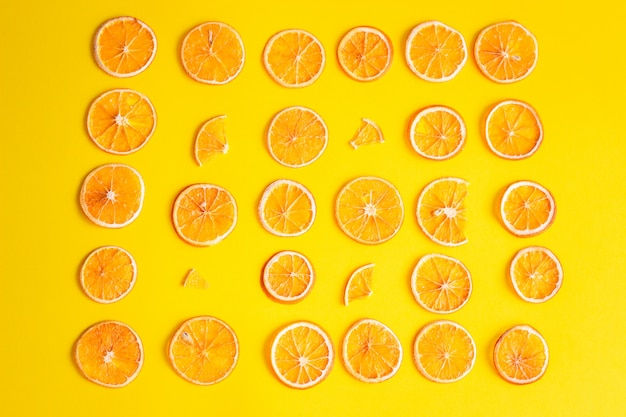 Creative pattern of dried orange slices. geometric pattern of orange slices on color