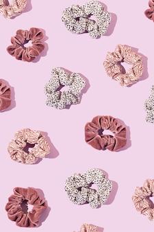 파스텔 핑크색 배경에 다양한 헤어 고무 밴드로 만든 창의적인 패턴입니다.