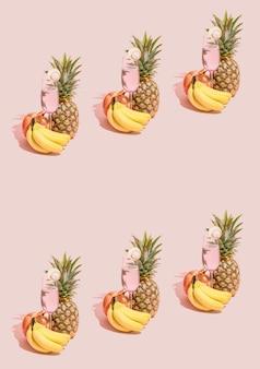 パステルピンクの背景にガラスの新鮮なバナナ、パイナップル、ザクロ、リフレッシュメントジュースで作られた創造的なパターン。自然な緑の植物の影。夏のトロピカルフレームコピースペース..