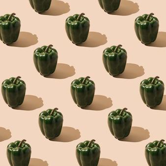 パステルカラーの背景に新鮮な緑の有機ピーマンで作られた創造的なパターン最小限の食品の概念