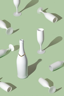 Creative pattern made with white champagne bottle and champagne glasses.