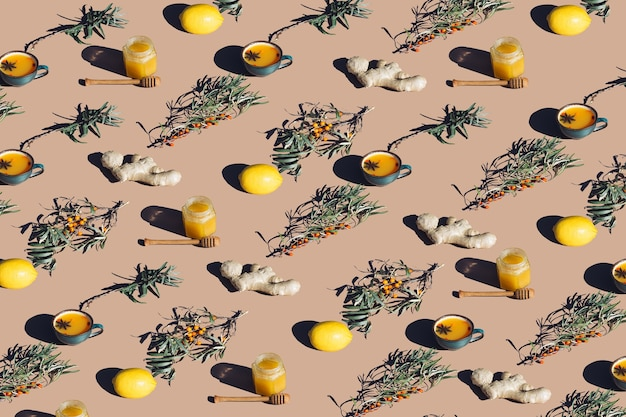 베이지색 배경에 바다 갈매나무, 생강, 레몬, 꿀의 창의적인 패턴입니다. 독감 시즌에 감기 예방 키트의 최소 레이아웃