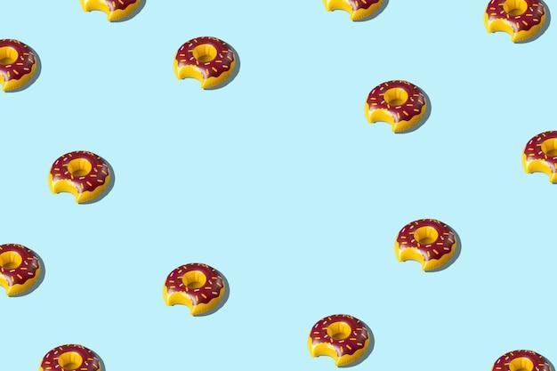 Творческий образец с надувной игрушкой пончика на синем фоне.