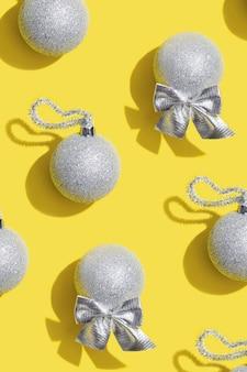 노란색 크리스마스 인사말 카드에 은색 새해 공 휴일 장난감이 있는 창의적인 패턴