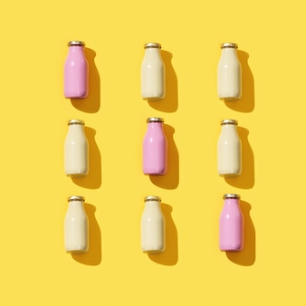 Creative pattern with small glass bottles for juice with hard light.