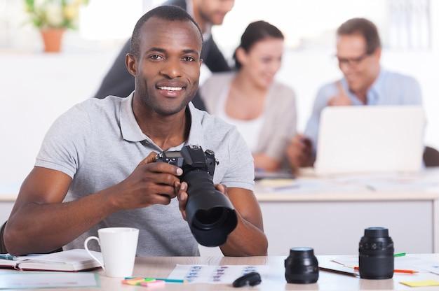 직장에서 창의적인 사람들. 카메라를 들고 세 사람이 배경 작업을 하는 동안 웃고 있는 잘생긴 젊은 아프리카 남자