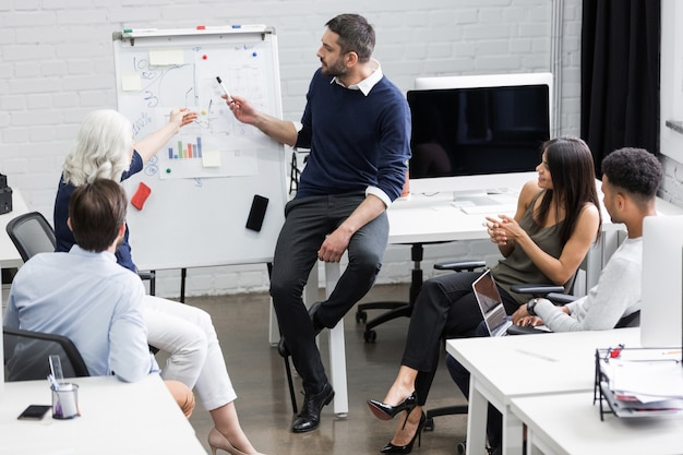 Творческие люди сидят за столом в зале заседаний