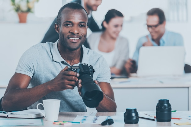 Creative people at work. handsome young african man holding camera and smiling while three people working on background
