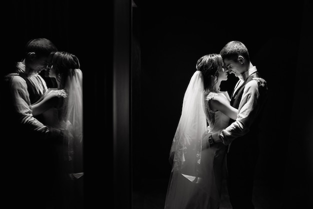 Creative photo idea of wedding photography in reflection. bride and groom illuminated by a lights.