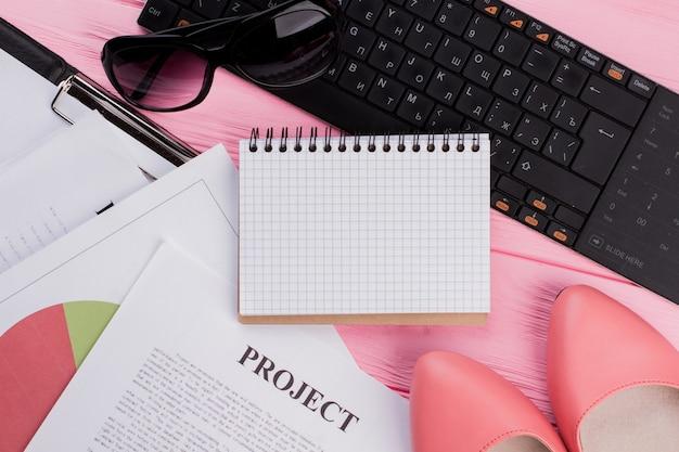 ピンクの背景に美しいフェミニンなアクセサリーレディースシューズメガネとクリエイティブな写真