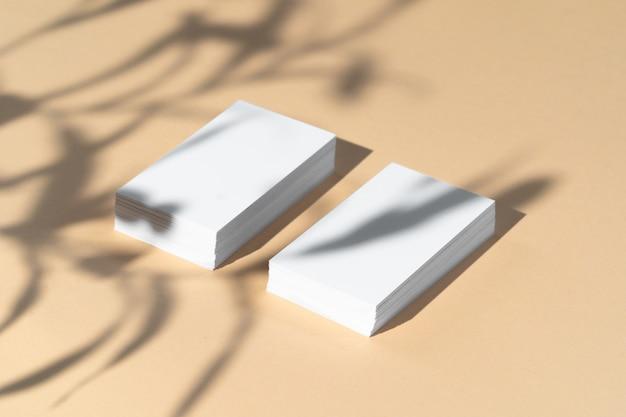 Креативное фото с цветочной тенью белой визитки на бежевом фоне