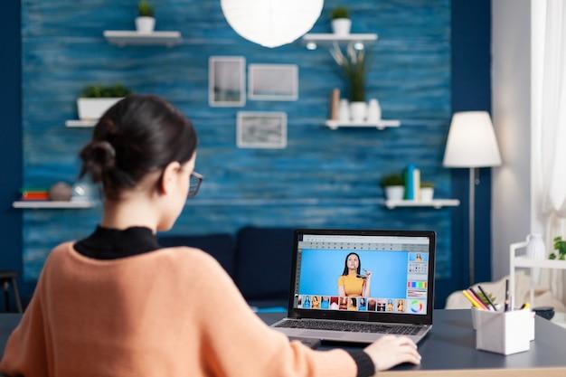クリエイティブフォトグラファーの学生がカラーグレードを変更しながら写真を編集し、ラップトップコンピューターを使用して写真をレタッチします。写真のデザインを勉強しているリビングルームの机のテーブルに座っている若い編集者