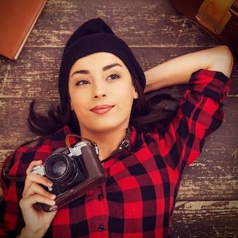クリエイティブな写真家。床に横たわって、スーツケースとメモ帳が彼女の近くに横たわっている間カメラを保持している帽子の美しい若い女性の上面図