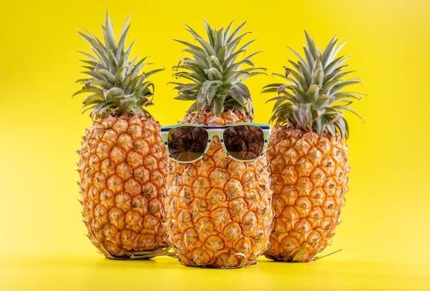Креативный ананас смотрит вверх в солнцезащитных очках и изолированной ракушке, пляж летних каникул