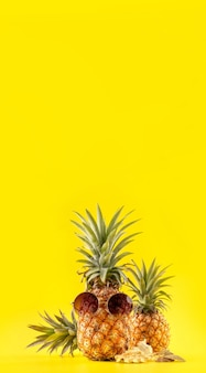 Creative pineapple looking up with sunglasses and shell isolated on yellow background, copy space close up