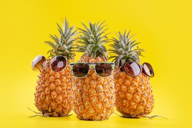 黄色の背景に分離されたサングラス、夏休みのビーチのアイデアデザインパターン、コピースペース、クローズアップ、テキストの空白で創造的なパイナップル