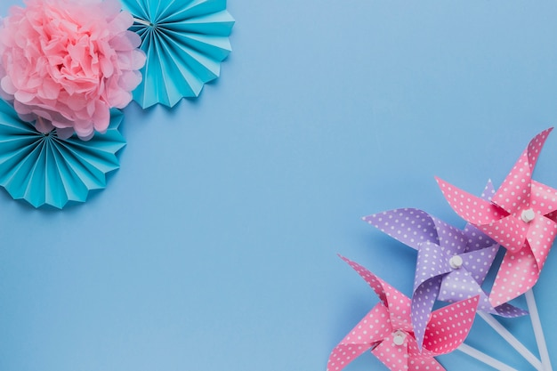 Creative pinwheel and beautiful paper flower at the corner of plain background