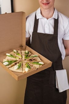 Creative pizza with flowers tulips in paper box served by waiter