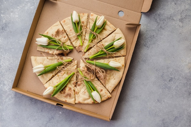 Creative pizza with flowers tulips in paper box