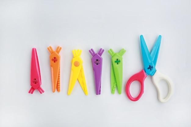 Creative plastic children safety scissors set on white background.