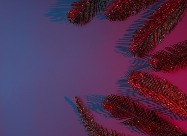 Creative pop art tropical concept. golden palm leaves on blue-red neon gradient background.