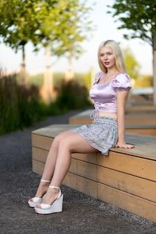 짧은 상의와 치마를 입은 크리에이 티브 초상화 금발 여자. 디자인 컨셉입니다. 도시 공원에서 쉬고 있는 젊은 여성의 낭만적인 초상화