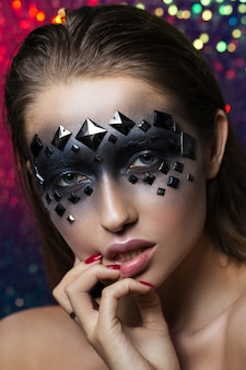 Creative portrait of a brunette with black eyes and rhinestones