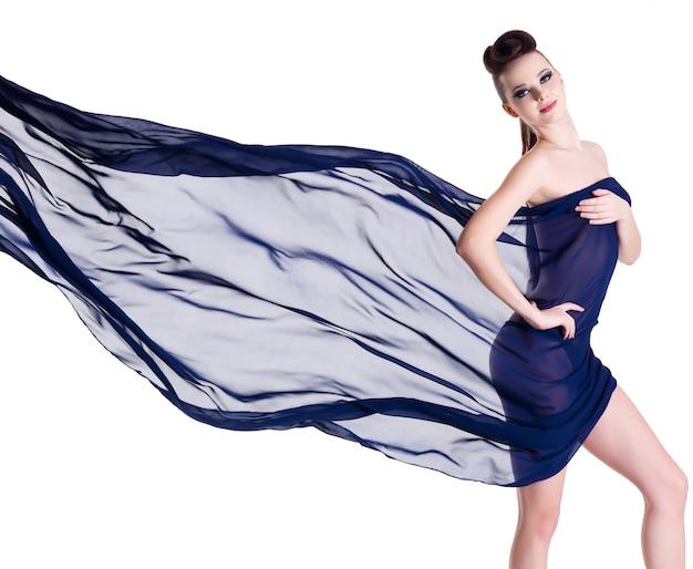 Ritratto creativo della donna di fascino di eleganza con chiffon blu che soffia su bianco