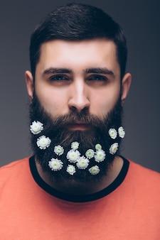Ritratto creativo di giovane uomo bello con la barba decorata con fiori.