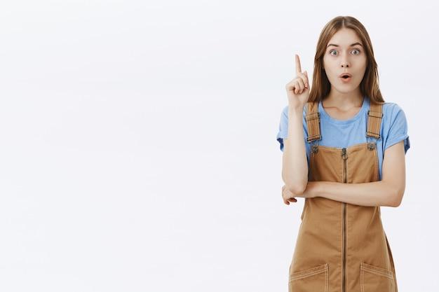 La bella ragazza creativa ha un'idea, alzando il dito suggerisce un piano
