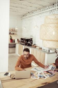창작 과정. 패션 디자이너가 식탁에 앉아 노트북을보고 자신의 작품을 확인하고 있습니다.